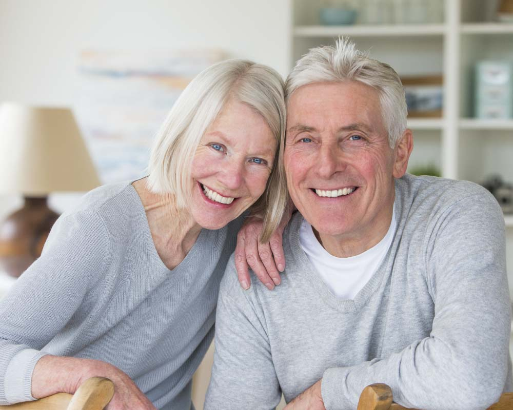 Senior couple in gray sweaters smiling showing off strong dental implants