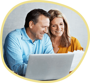 Man in a blue shirt and woman in a yellow shirt sitting in front of a computer smiling as they look through their financial options for dental care.