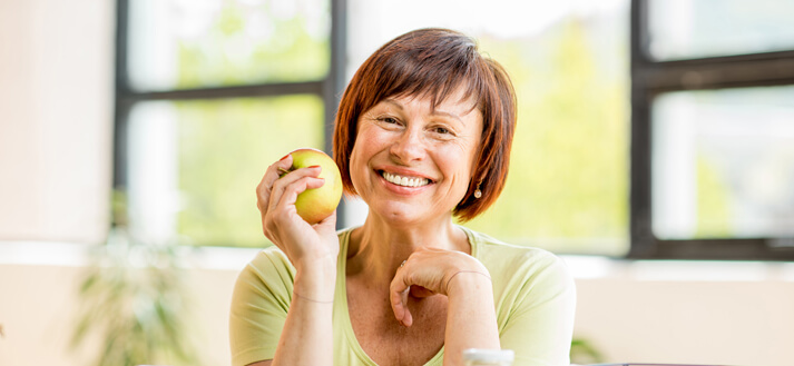 woman with brown hair and brown eyes in a lime green shirt smiling while holding a yellow apple.