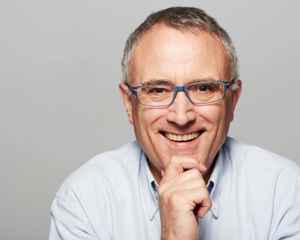 Senior man wearing glasses and smiling showing off dental implants